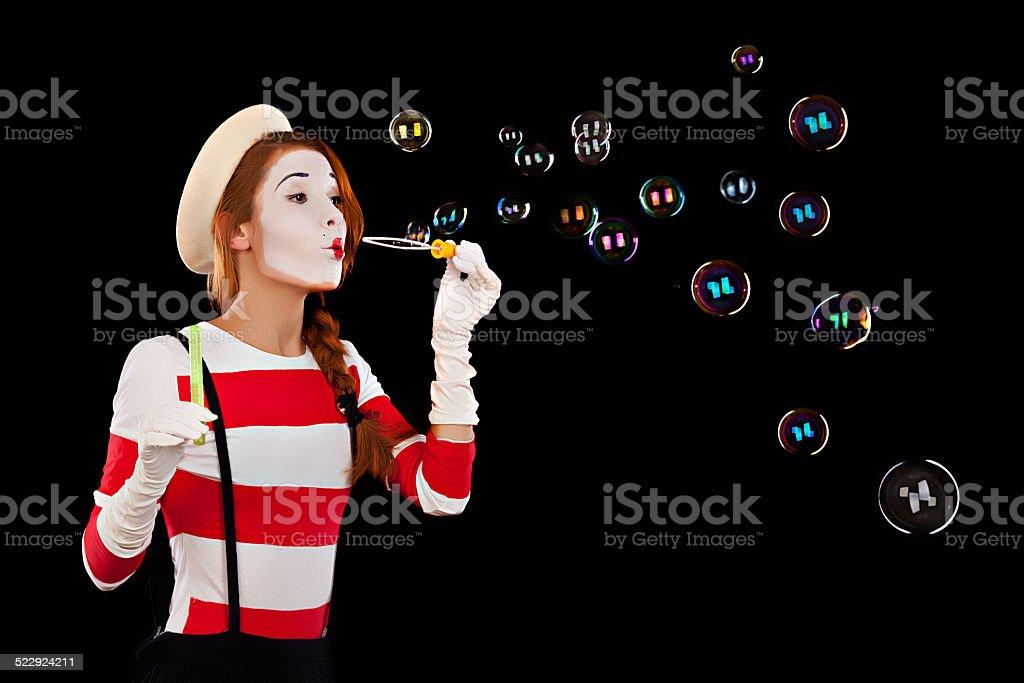 Portrait of the female MIM comedian blows soap balls stock photo