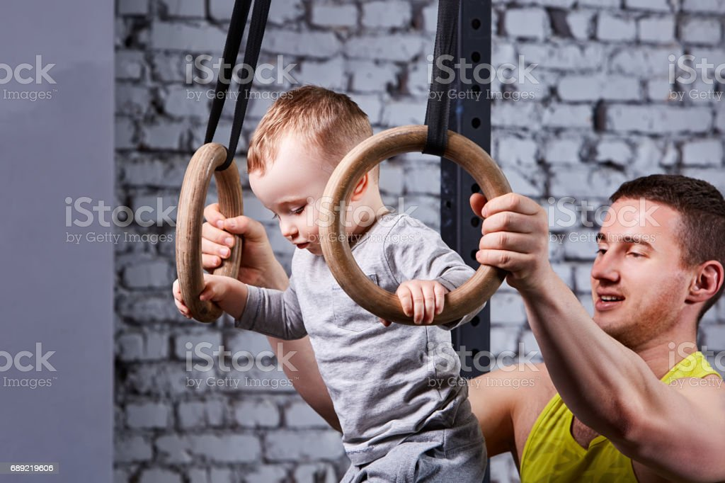 Portrait of the happy young father trains the little son with gimnastic rings against brick wall in the gym. stock photo
