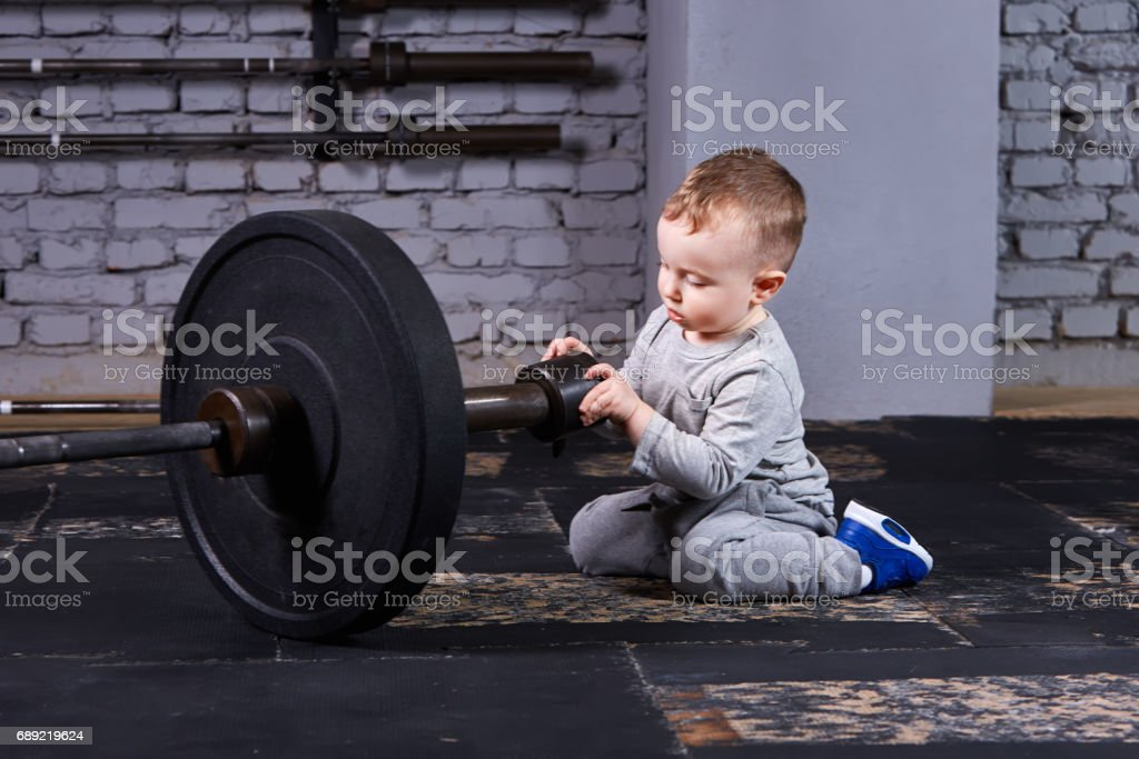 Portrait of the little boy with dumbbells against brick wall at the    gym. stock photo