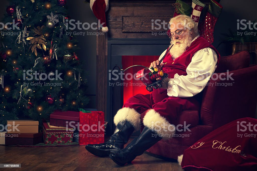 Portrait of the Real Santa Claus at home painting toys stock photo