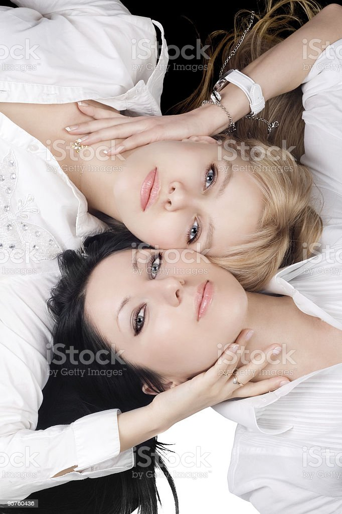 Portrait of the two lying pretty girlfriends stock photo