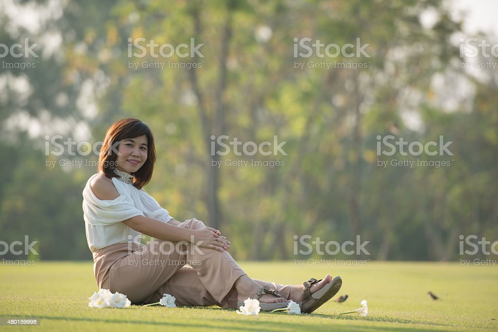 Portrait of the woman sitting in the green lawn garden stock photo