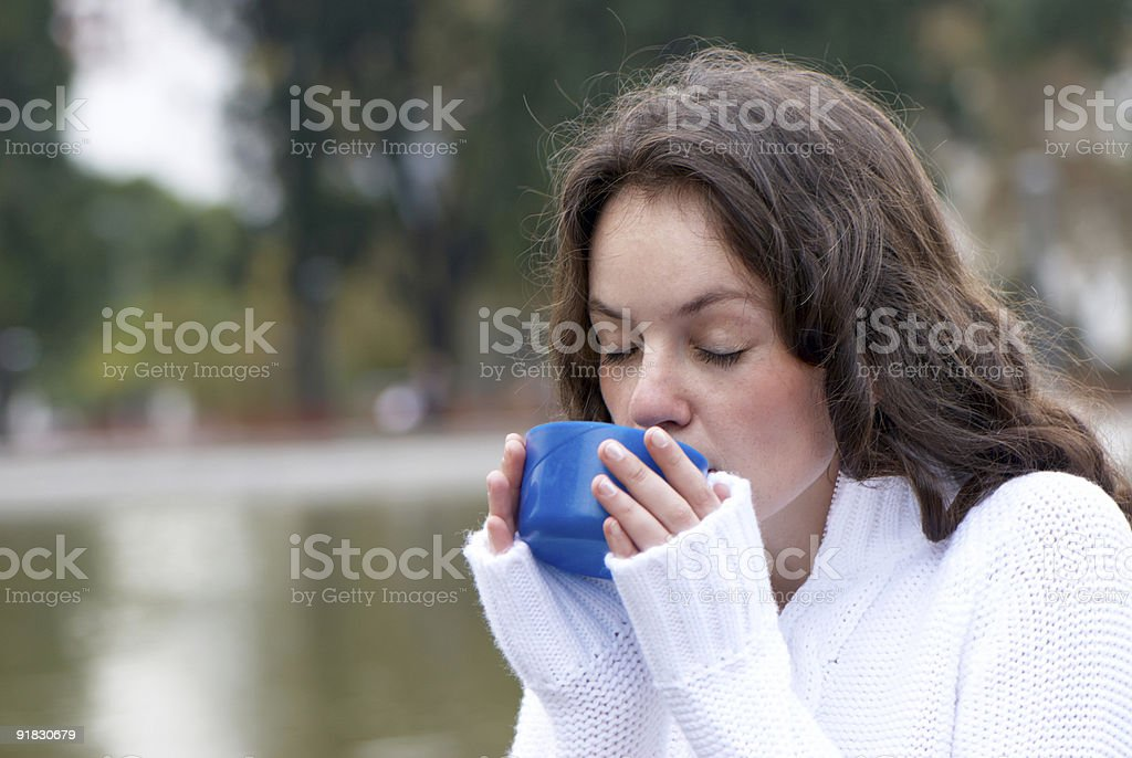 Portrait of the young woman drinking hot tea outdoors royalty-free stock photo