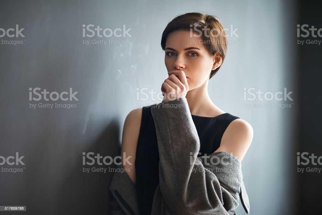 Portrait of thoughtful beautiful woman on dark background stock photo