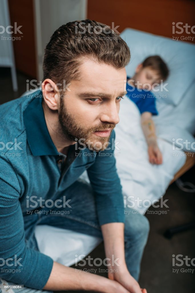 portrait of thoughtful dad sitting near sick son in hospital bed stock photo
