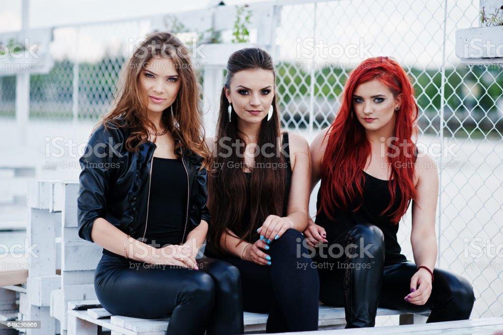 Portrait of three fashion girls sitting on bench at pier stock photo