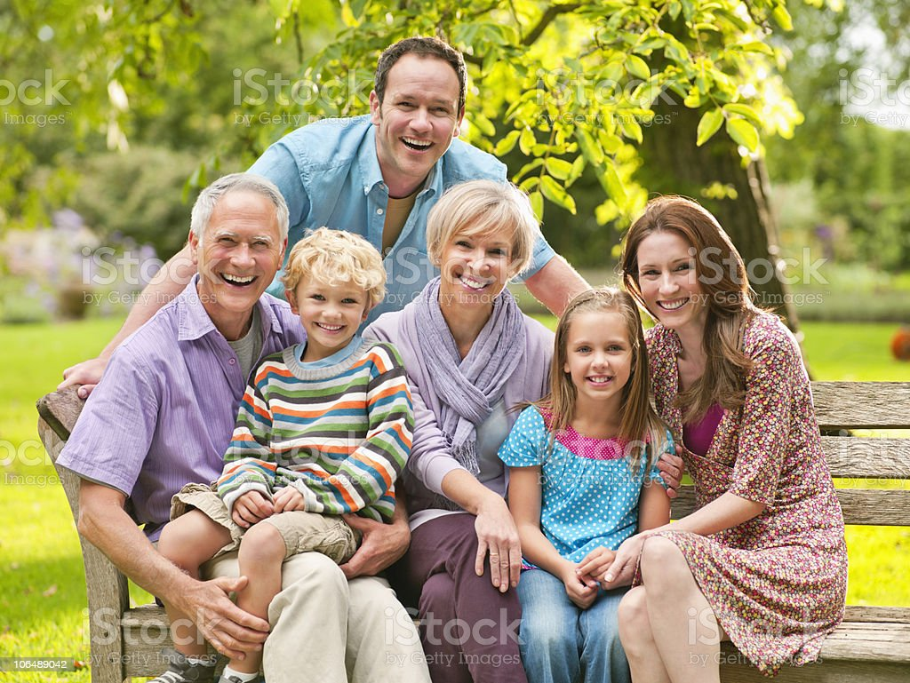 Portrait of three generation family sitting on bench at park royalty-free stock photo