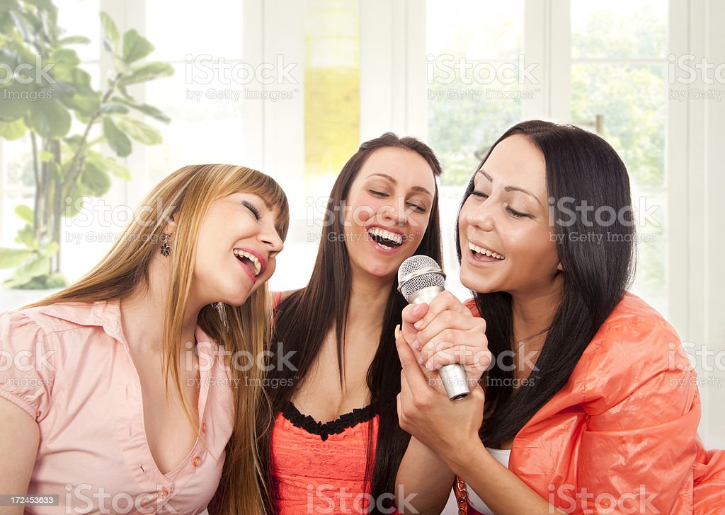 Portrait of Three girl  Singing with Microphone royalty-free stock photo