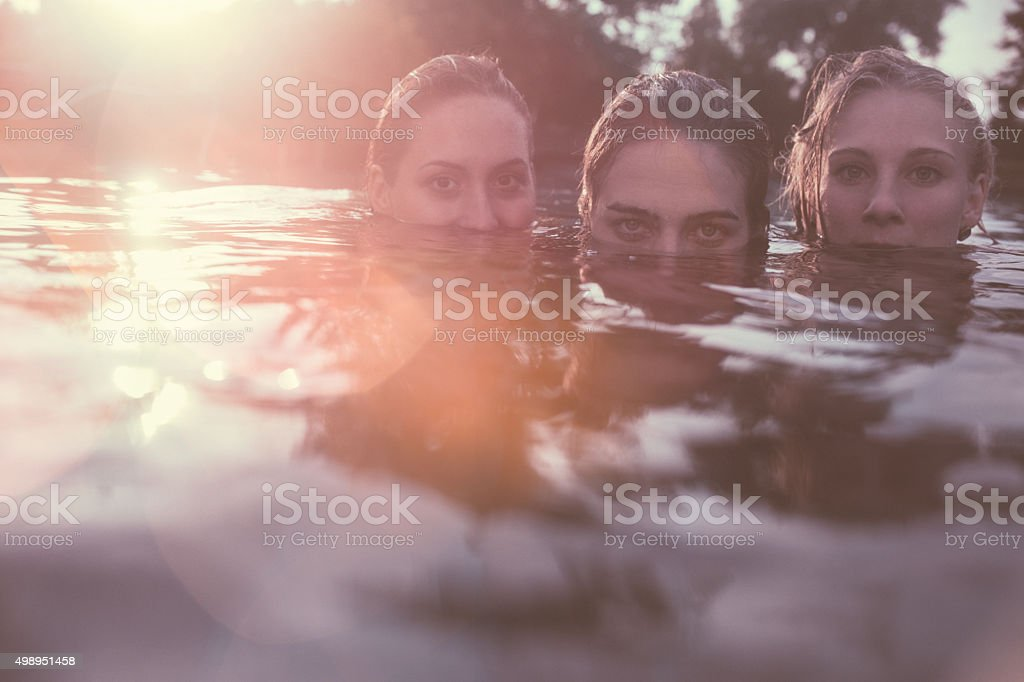 Portrait of three girls submerged in swimming pool at sunset stock photo