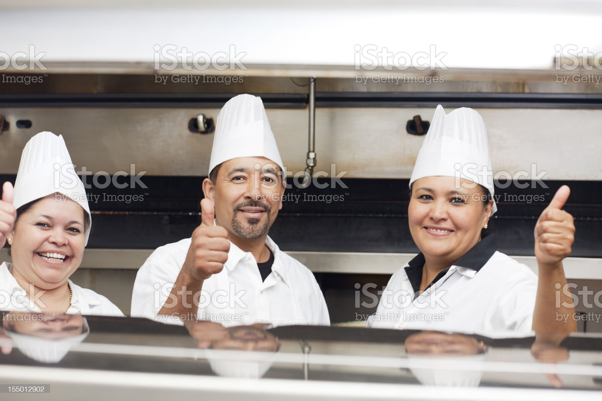 Portrait of three happy smiling chefs inside the restaurant kitchen royalty-free stock photo
