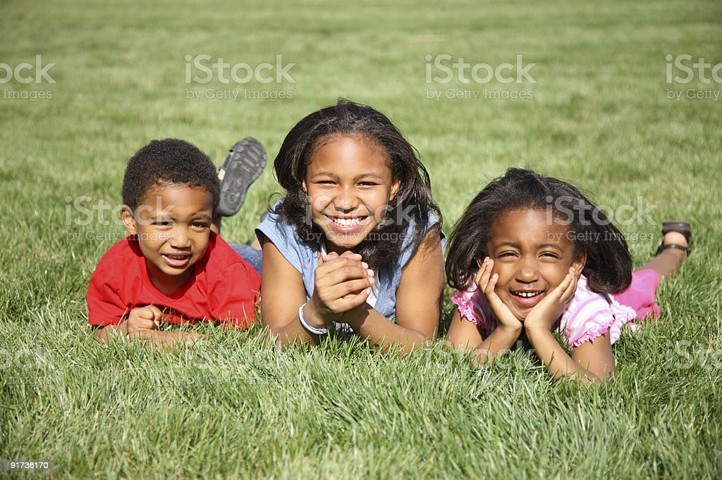 Portrait of three kids laying in grass royalty-free stock photo