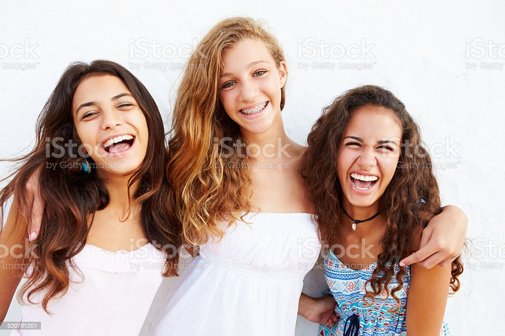 Portrait Of Three Teenage Girls Leaning Against Wall stock photo