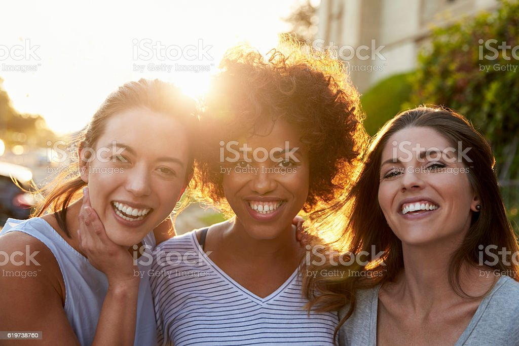 Portrait of three young adult female friends in the street stock photo