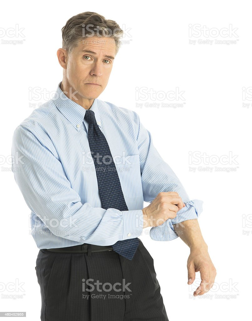 Portrait Of Tired Businessman Rolling Up His Sleeves stock photo