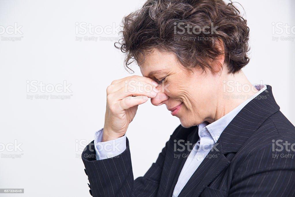 Studio portrait of tired senior Caucasian businesswoman rubbing eyes...
