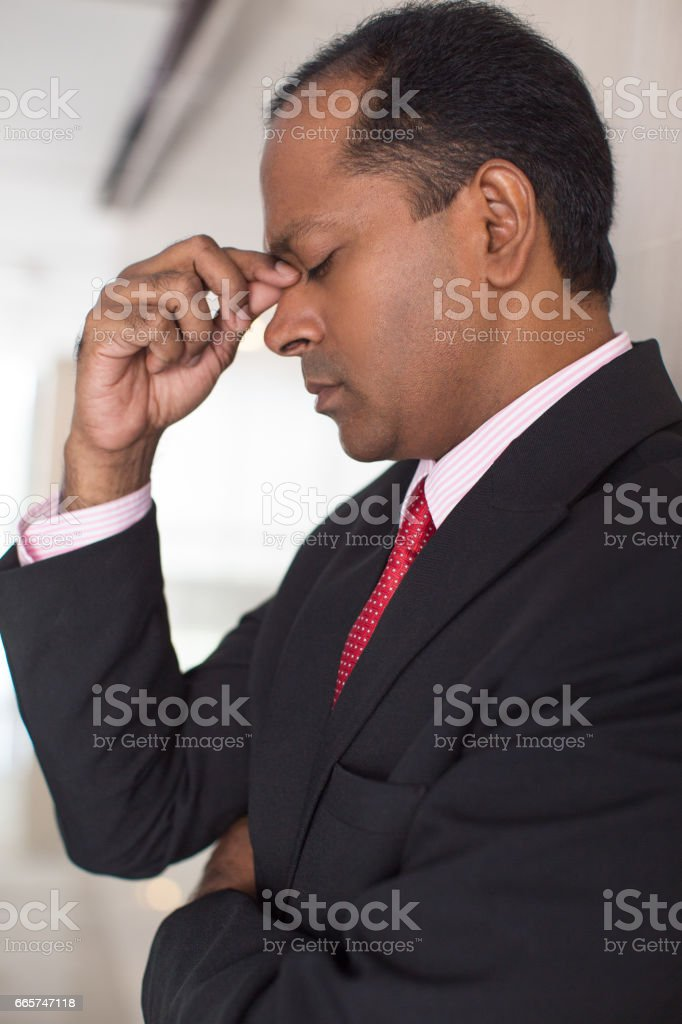 Portrait of tired mid adult Indian businessman rubbing eyes in...