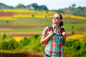 Portrait of traveler with backpack on background colored fields