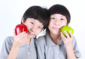 Portrait of two boys, twins holding red and green apples
