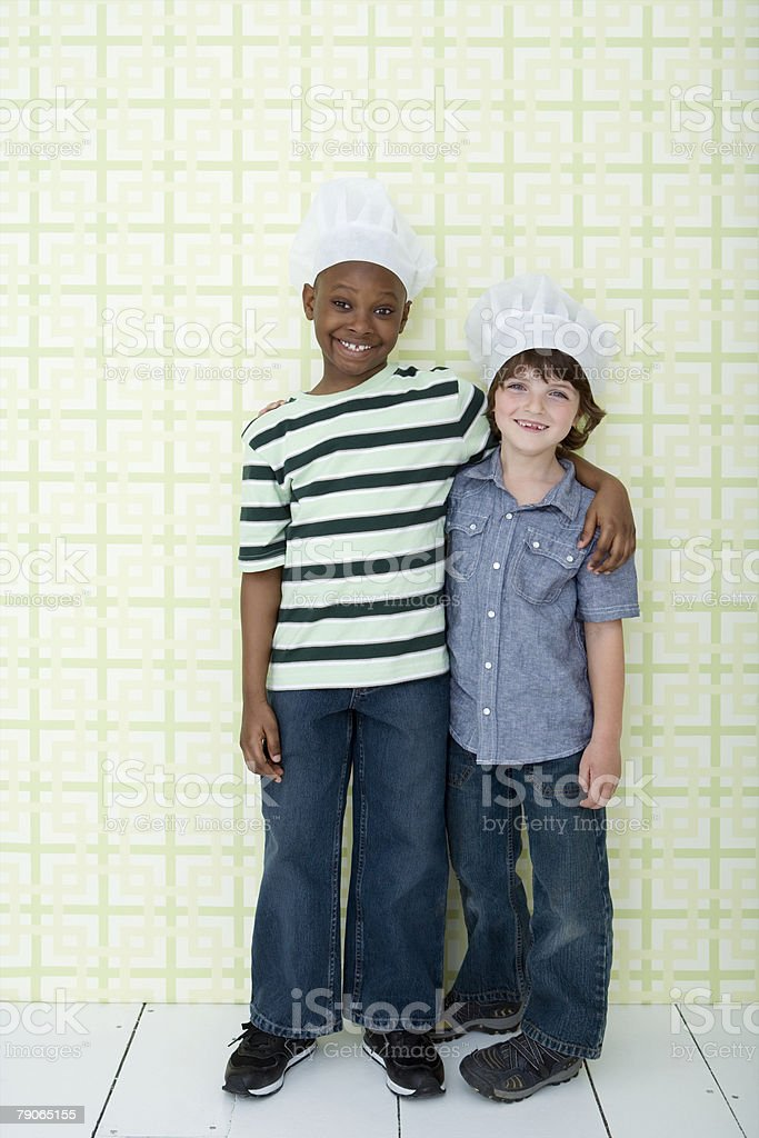 Portrait of two boys wearing chefs hats royalty-free stock photo