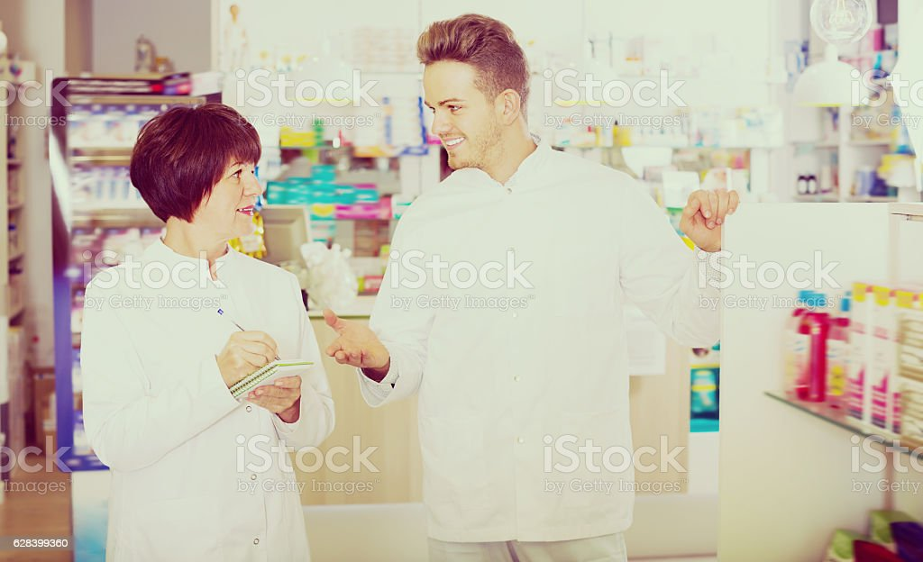 Portrait of two cheerful adult pharmacists stock photo