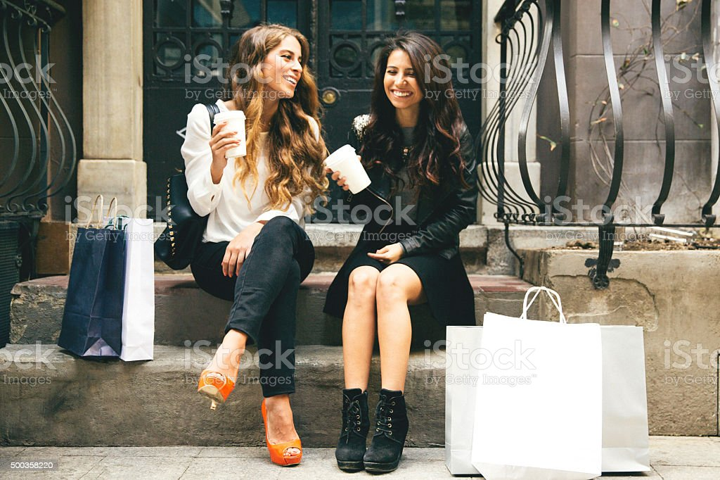 Portrait Of Two Cheerful Women Having A Break After Shopping stock photo