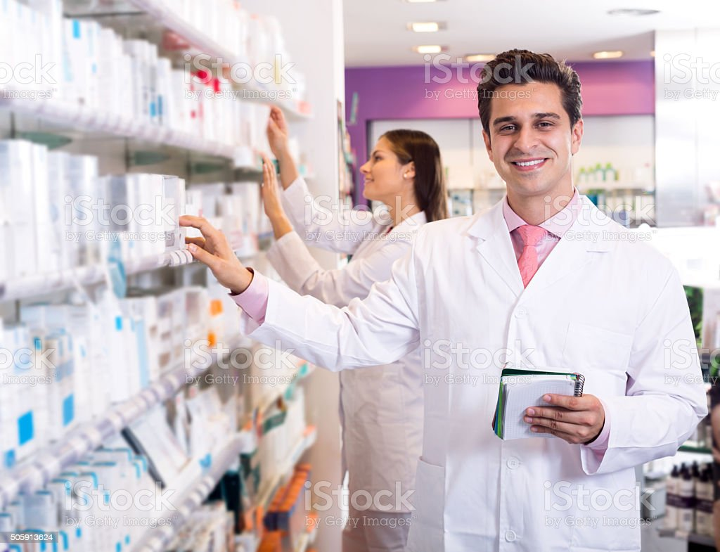 Portrait of two friendly pharmacists working stock photo
