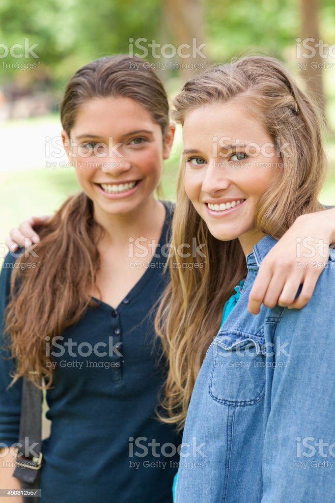 Portrait of two friends posing while holding each other royalty-free stock photo
