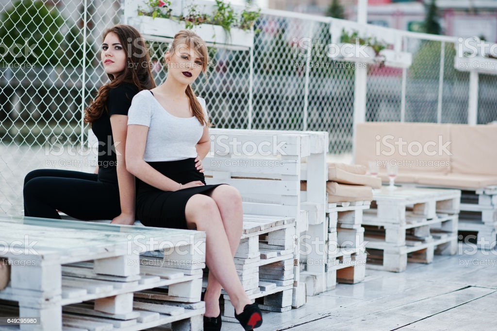 Portrait of two girls sitting on bench at pier stock photo