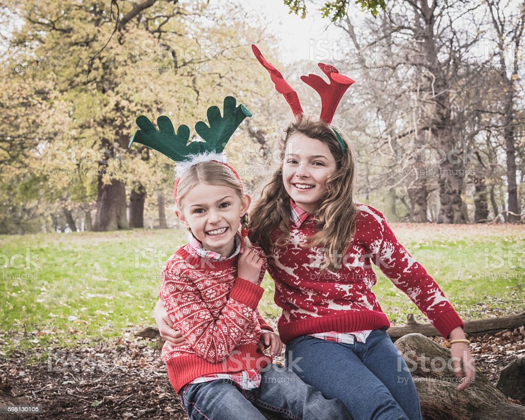 Portrait of two girls wearing antlers, arms around each other stock photo