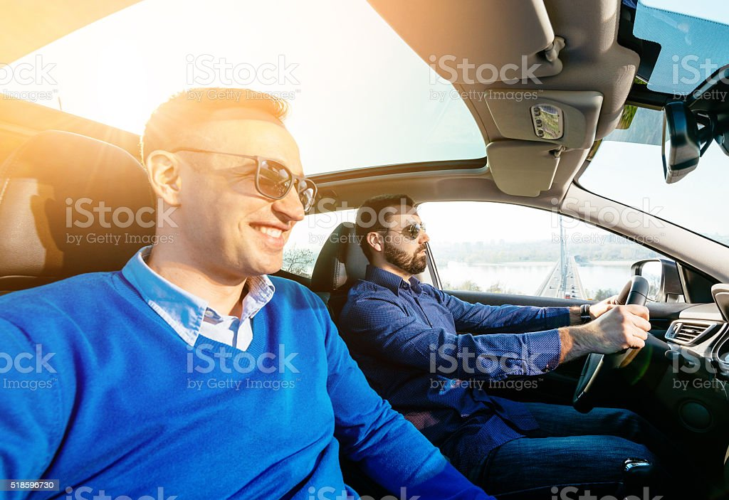 Portrait of two handsome men in car driving for holiday stock photo