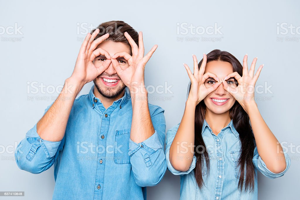 Portrait of two happy funny lovers holding fingers near eyes stock photo