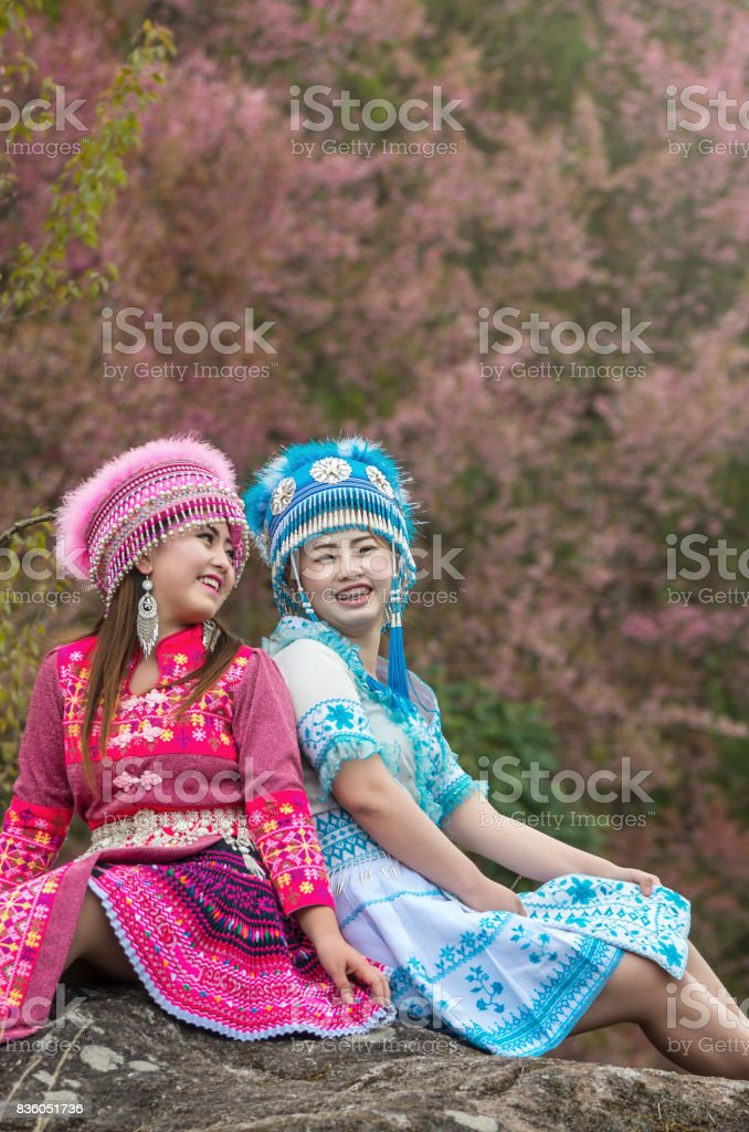 Portrait of Two Hmong girls with traditional Hmong suit on the Sakura blossom background, Chiang Mai province, Thailand. stock photo