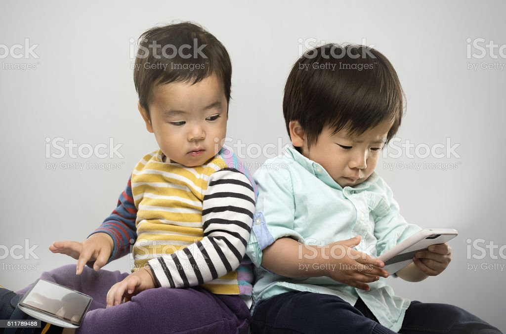Portrait of two japanese kids with their electronic devices. stock photo