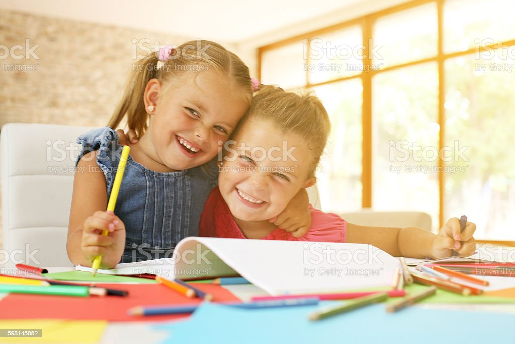 Portrait of two little girl drawing and looking at camera. stock photo