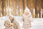 Portrait of two little girls play with snow in winter