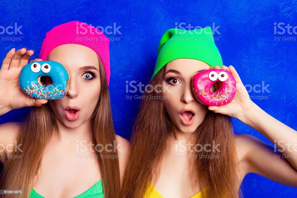 Portrait of two pretty shocked women holding donutes near eye stock photo