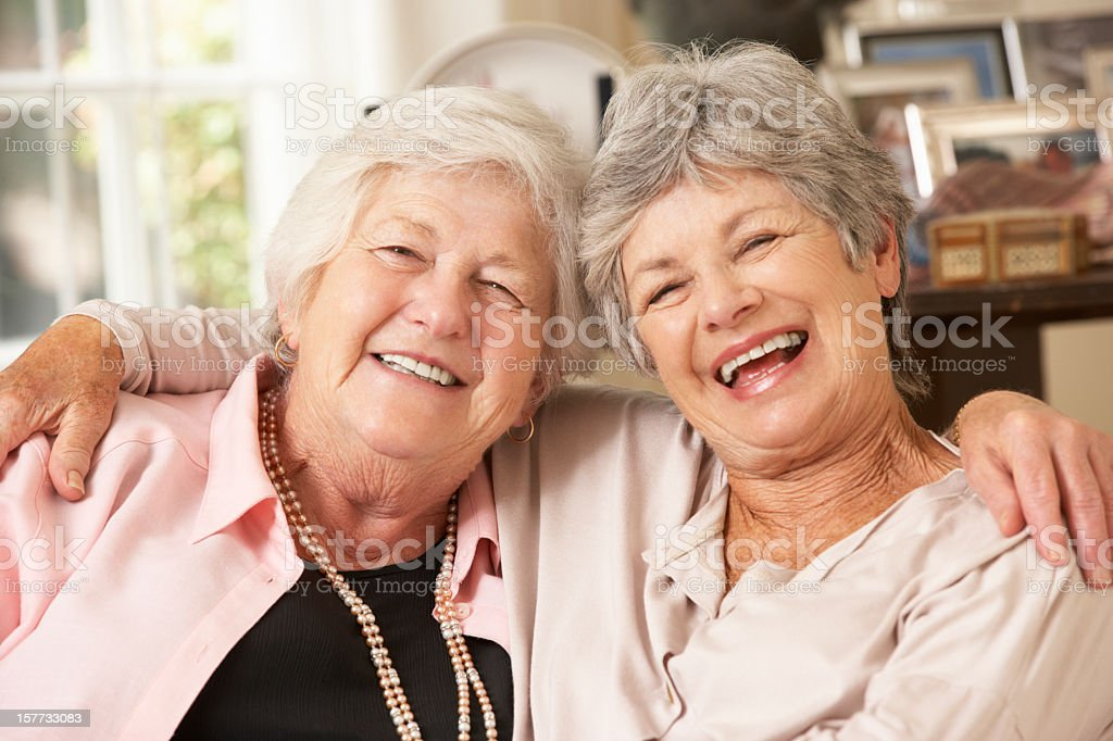 Portrait Of Two Retired Senior Female Friends Sitting On Sofa stock photo