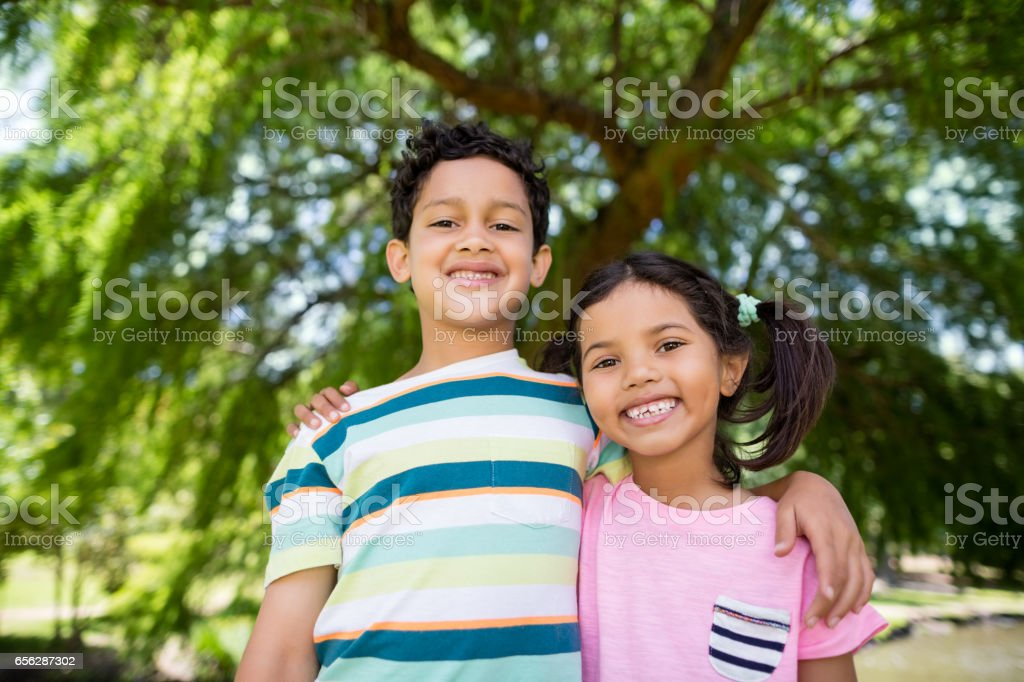 Portrait of two siblings standing together in park stock photo