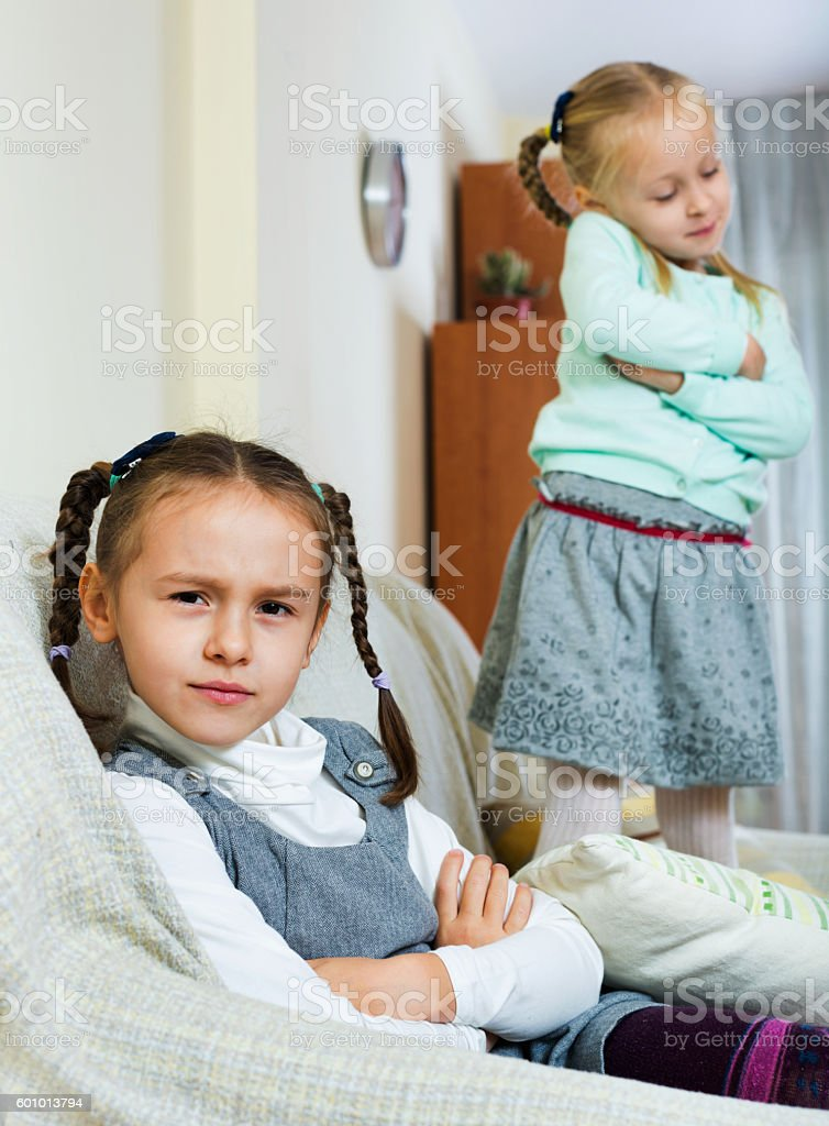 Portrait of two small miserable girls having conflict stock photo