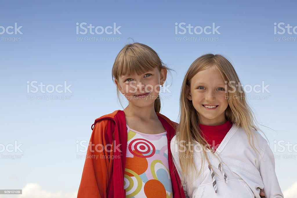 Portrait of two smiling girls  on the blue sky. stock photo