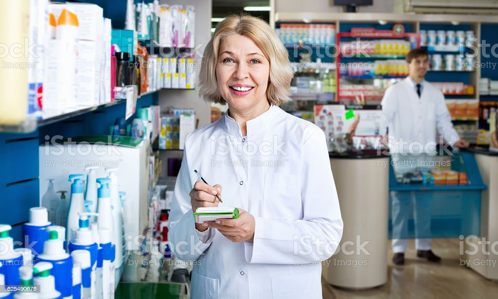 Portrait of two smiling pharmacists working in  farmacy stock photo