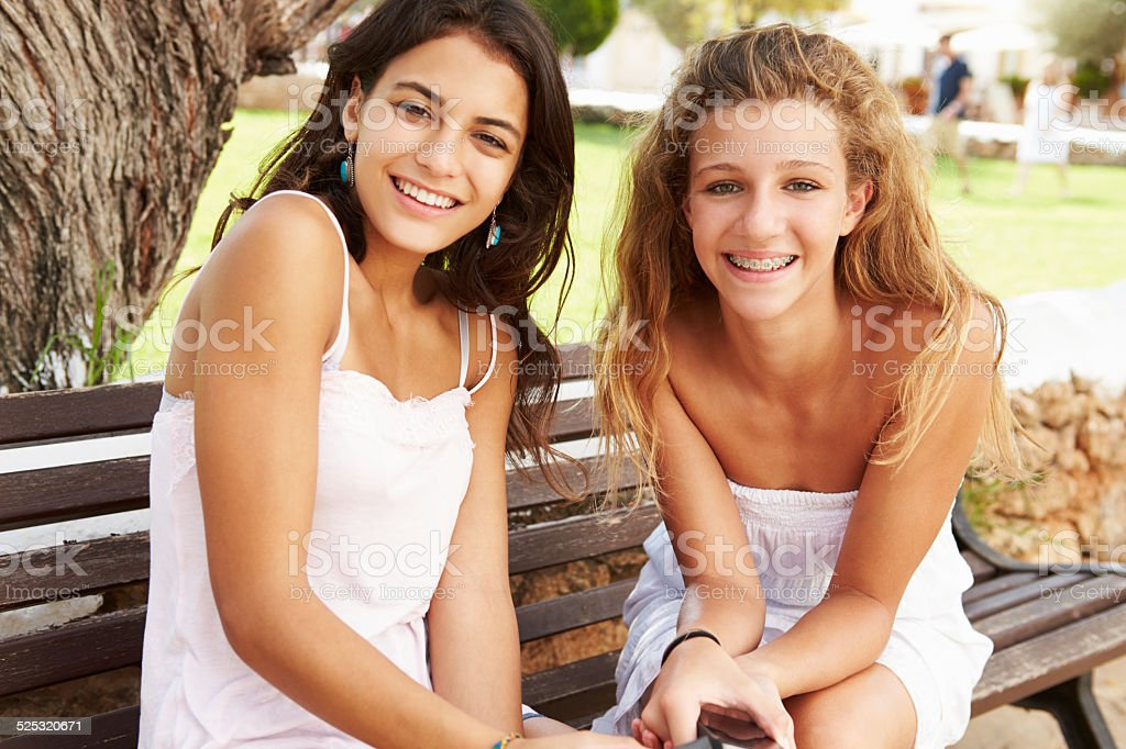 Portrait Of Two Teenage Girls Sitting On Park Bench Together stock photo