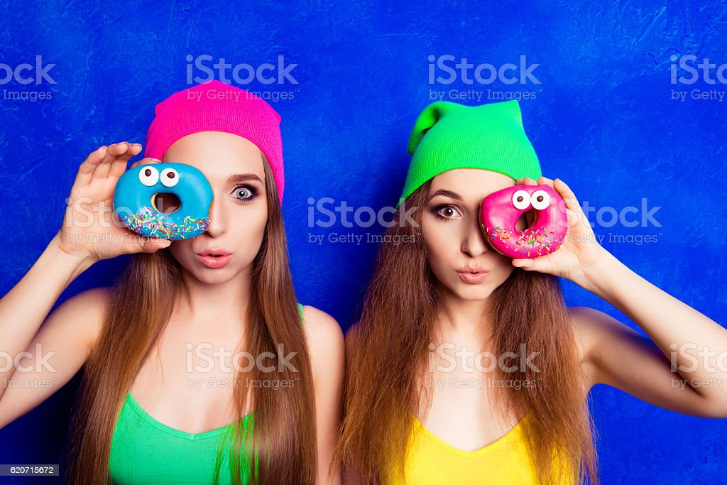 Portrait of two women pouting and  holding donutes near eye stock photo