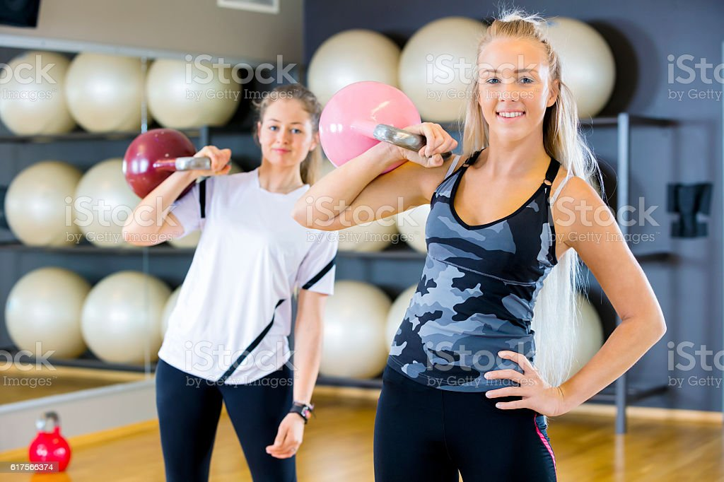 Portrait of two women with kettlebells at fitness gym stock photo