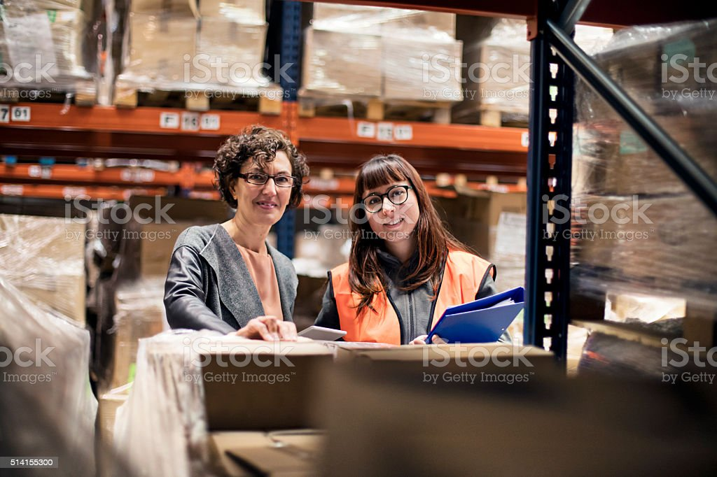 Portrait of two women working at a warehouse stock photo