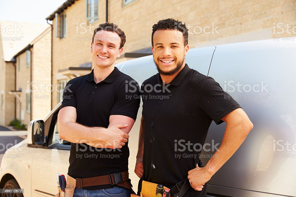 Portrait of two young tradesmen by their van stock photo