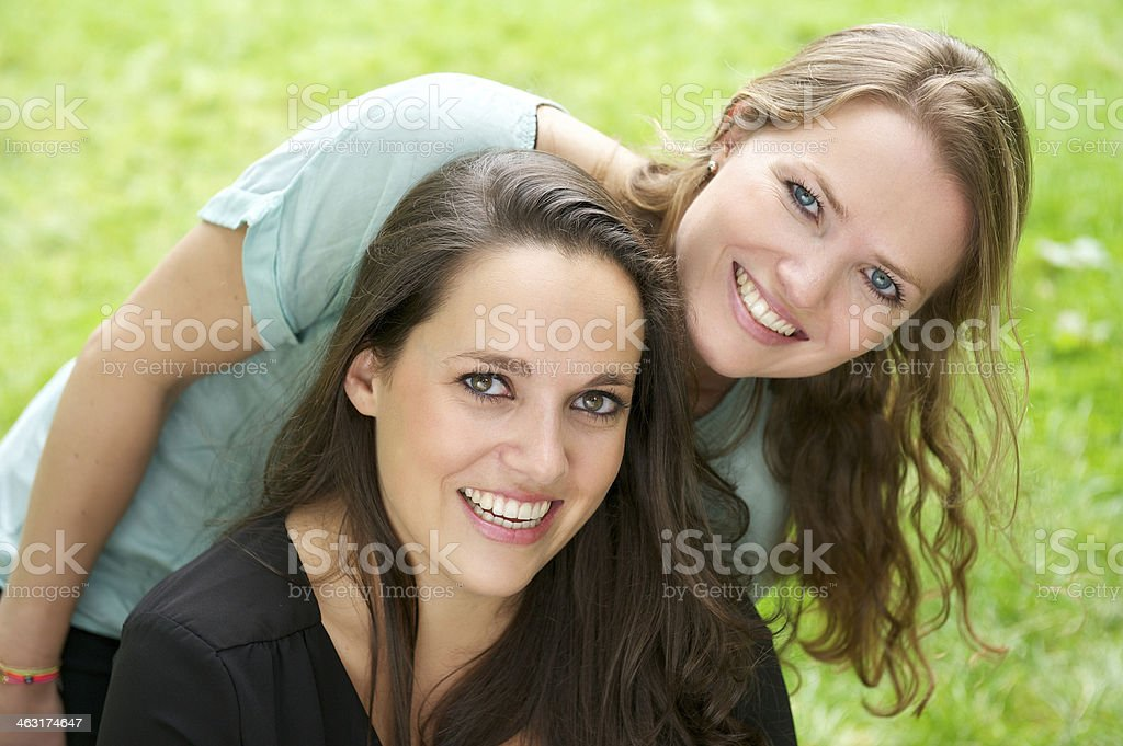 Portrait of two young women laughing outdoors stock photo