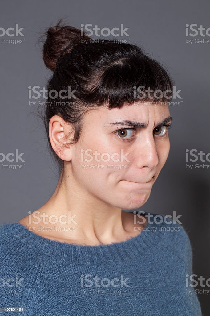 portrait of unhappy brunette girl expressing disagreement and doubt stock photo