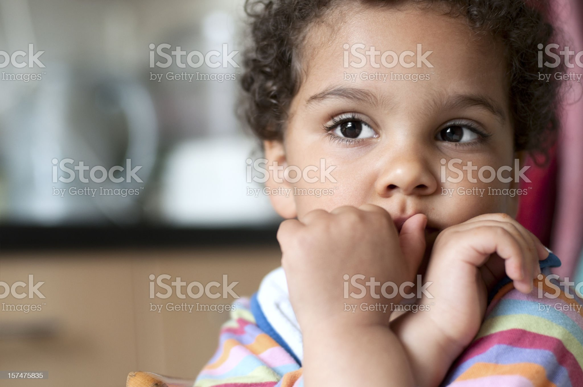 Portrait of Very Thoughtful Little Girl Sitting in Kitchen royalty-free stock photo