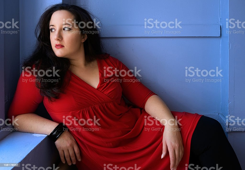 Portrait of Voluptuous Woman Wearing Red Dress and Posing stock photo